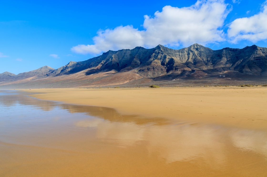 'Reflection of mountains in wet sand on Cofete beach in secluded part of Fuerteventura, Canary Islands, Spain' - Isole Canarie
